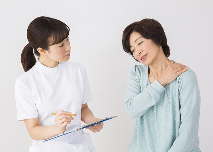 肩の不調を訴える女性と話を伺うスタッフ
