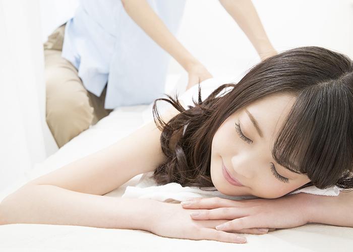 寝そべって整体の施術を受ける女性