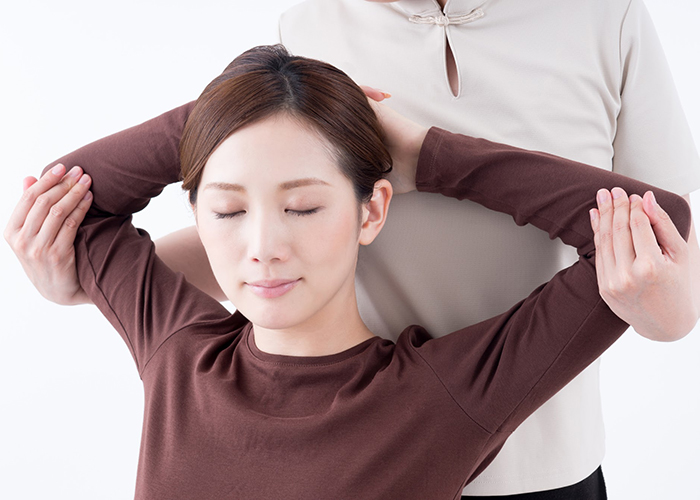 肩周りの整体の施術を受ける女性